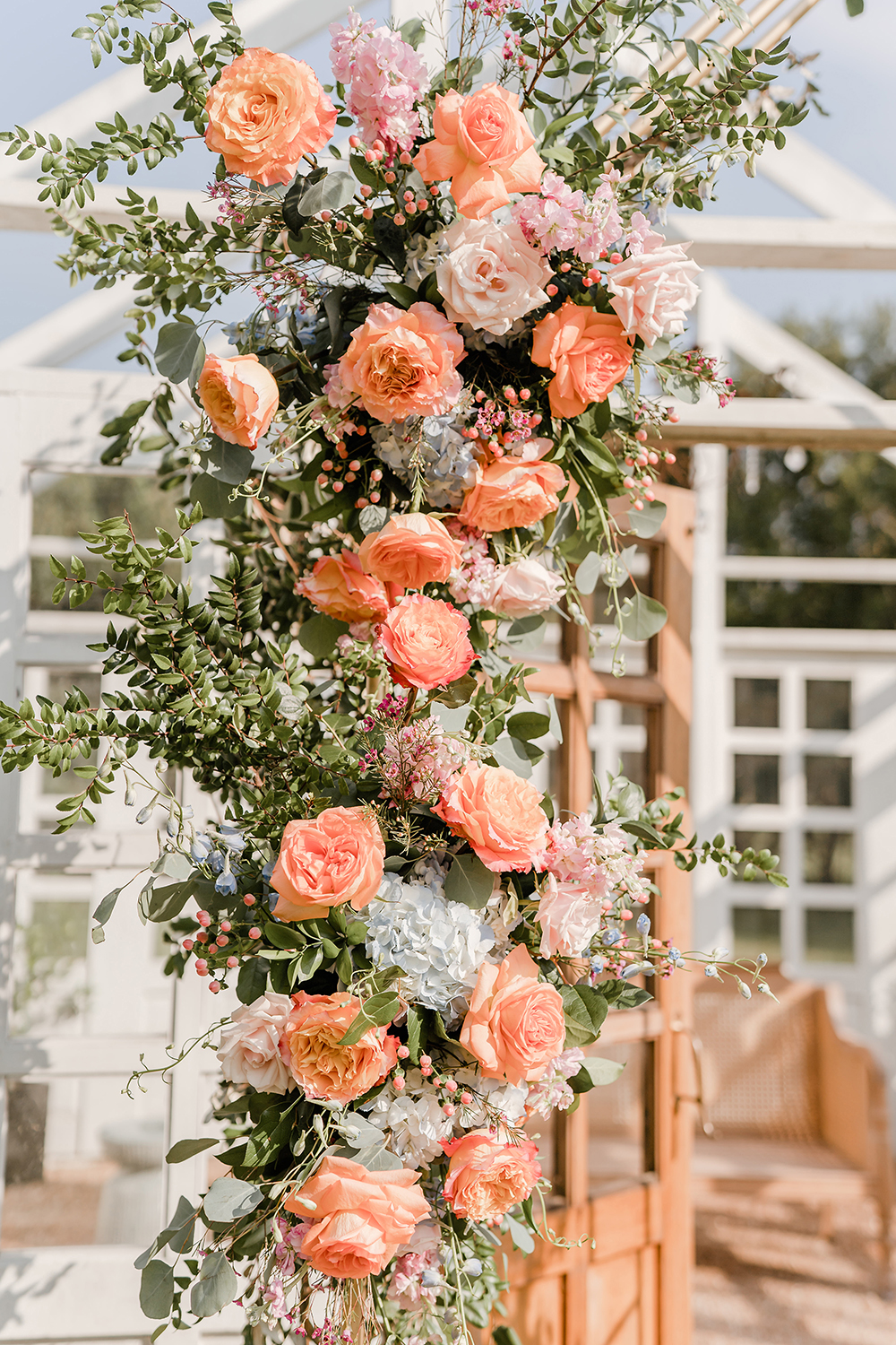 A floral arrangement alongside a white atrium made up of Silver dollar Eucalyptus, Huckleberry, Italian and Isralie Ruscus, Free Spirit Roses, Sweet Eskimo Roses, LightBlue Delphinium, Raspberry Wax Flowers, Pink Stock, Coral Hyperium Berries, and Light Blue Hydrangea.