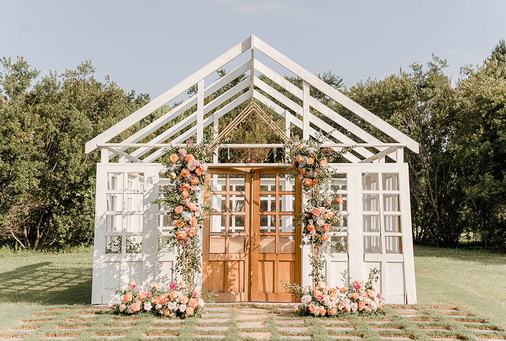 Whit atrium house with open doors and wooden tall windows decorated with bright floral decor on the wooden door.
