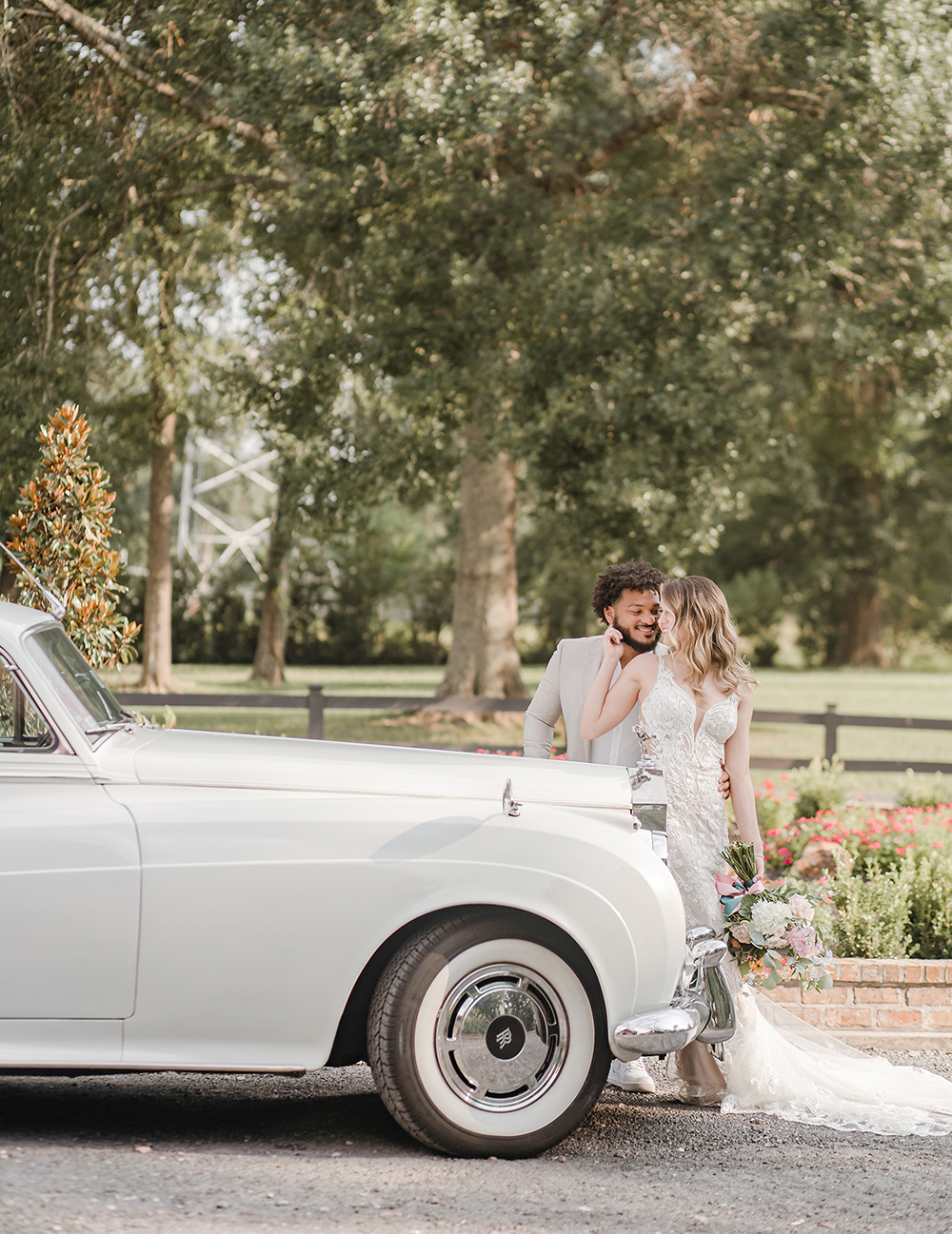 A man in a cream colored suit stands behind a woman in a long lace wedding gown next to a vintage white Rolls Royce on the property of wedding venue, The Carriage House, at a wedding styled shoot.