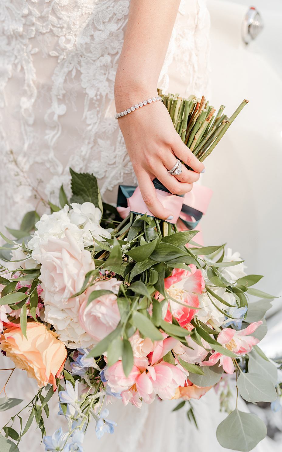 A pastel colored wedding bouquet provided by Dream Bouquet held by a hand wearing a diamond ring, stacked wedding band and a diamond tennis bracelet at a wedding styled shoot at The Carriage House wedding venue.