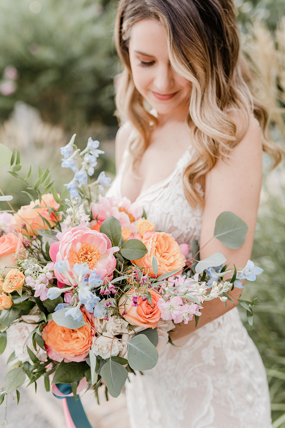 Model in lace white gown looking down at a pastel colored bouquet filled with pink peonies, light blue hydrangea twigs, pink stock, orange roses, and eucalyptus at a wedding styled shoot at wedding venue, The Carriage House.