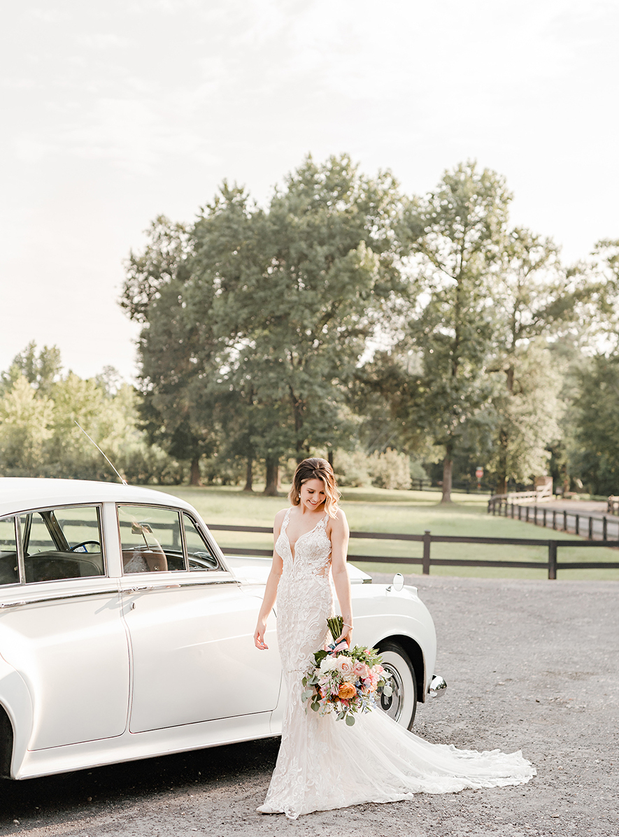 A woman with long wavy blonde hair wearing a fitted lace gown looks down at the bouquet she is holding next to an old fashioned Rolls Royce on the gravel road leading to the wedding venue, The Carriage House.