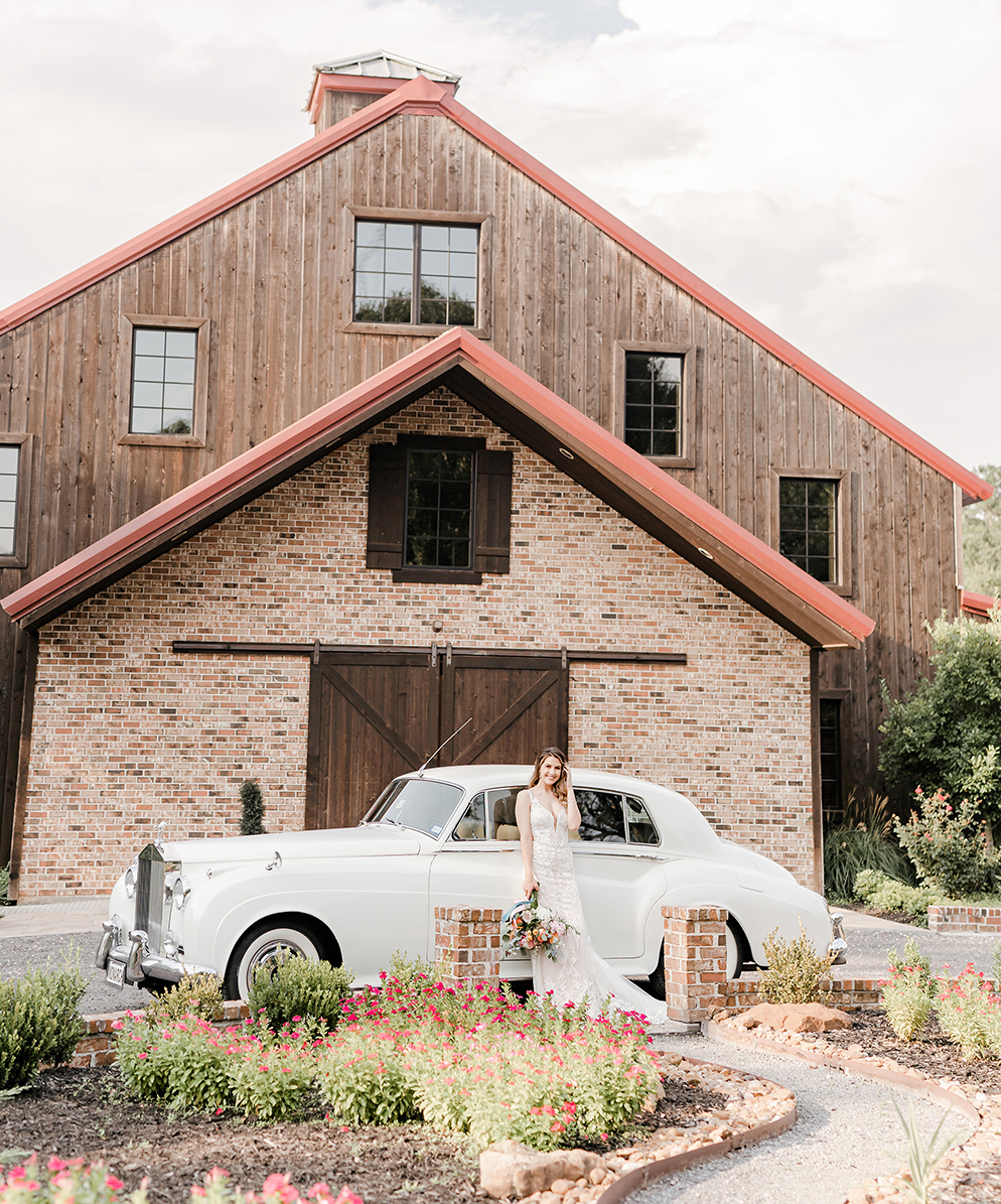 Woman in long lace wedding gown holding a bouquet next to a vintage Rolls Royce outside of a brick and wood barn style building at the Conroe area wedding venue, The Carriage House.