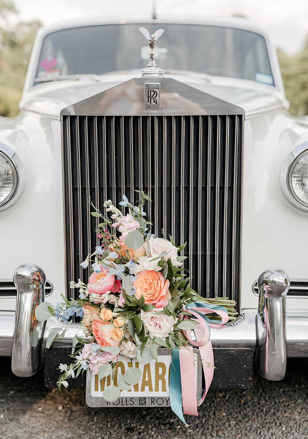 A bouquet sit on the front bumper of an ivory old fashioned rolls royce from Monarch Limo.