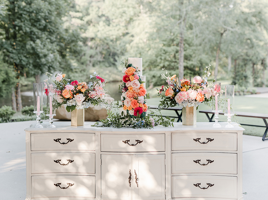 A white buttercream cake with fresh bright floras and lit light pink tapered candles atop of a cream colored white chest of drawers on a shaded concrete patio of wedding venue, The Carriage House.