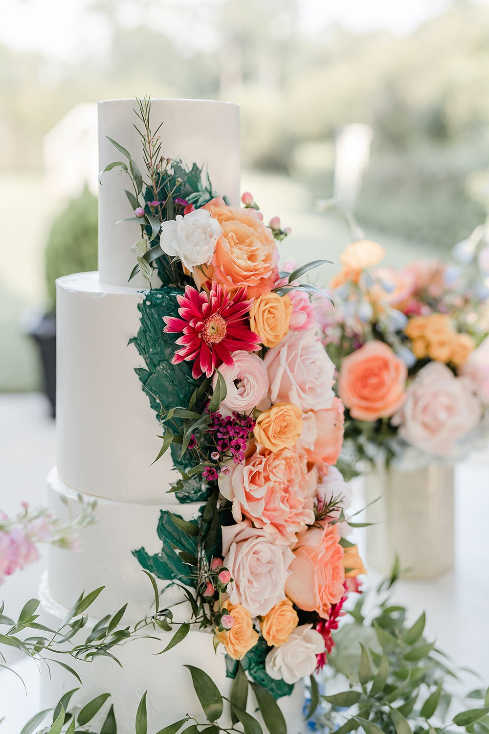 A white butter cream four tiered cake adorned with fresh flowers by Marblelous Cakes.