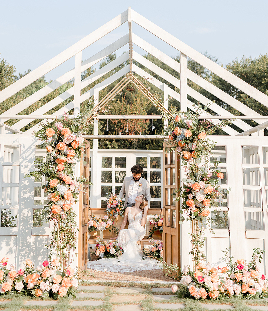 Man leaning over a bench kissing a woman in a long white gown inside a white outdoor structure adorned with orange, red and blush colored blooming florals and greenery on the lawn of the Carriage in Conroe, Texas.
