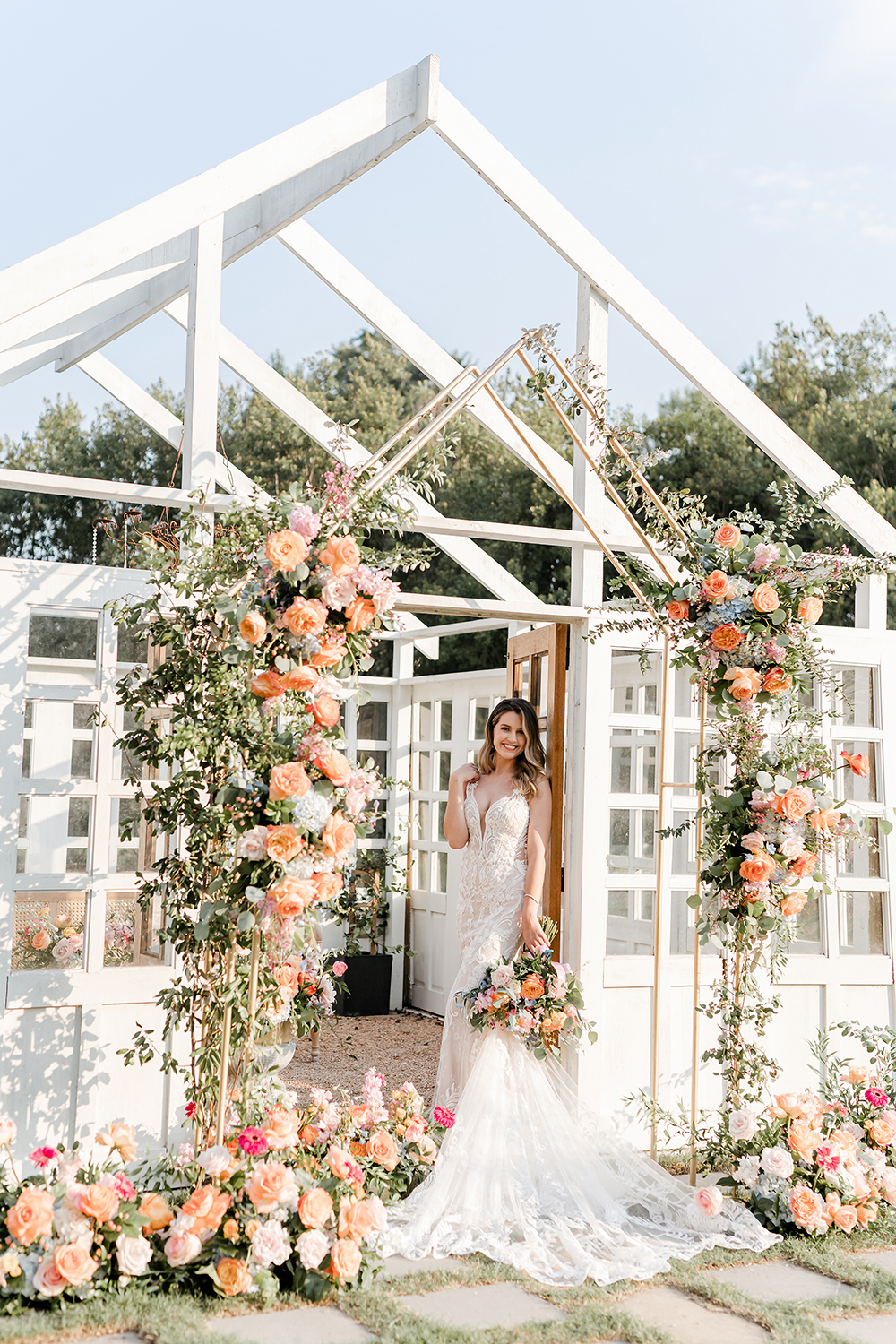 A bride in a white lace fitted gown holding a floral bouquet that matched the floral decor all around her in a white atrium full of glass windows.