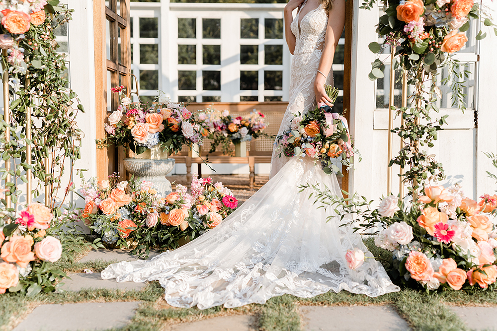 A white lace wedding dress train flows on the stones that lead to a white atrium covered in florals that include orange rose, coral carnations, light blue hydrangeas, and light pink peonies.