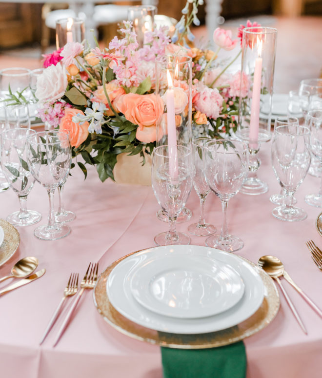 Round table with pink tablecloth set with white and gold placesettings, dark green napkins, lit pink tapered candles and a fresh floral centerpiece with garden roses, peonies and greenery inside a reception space at The Carriage House.