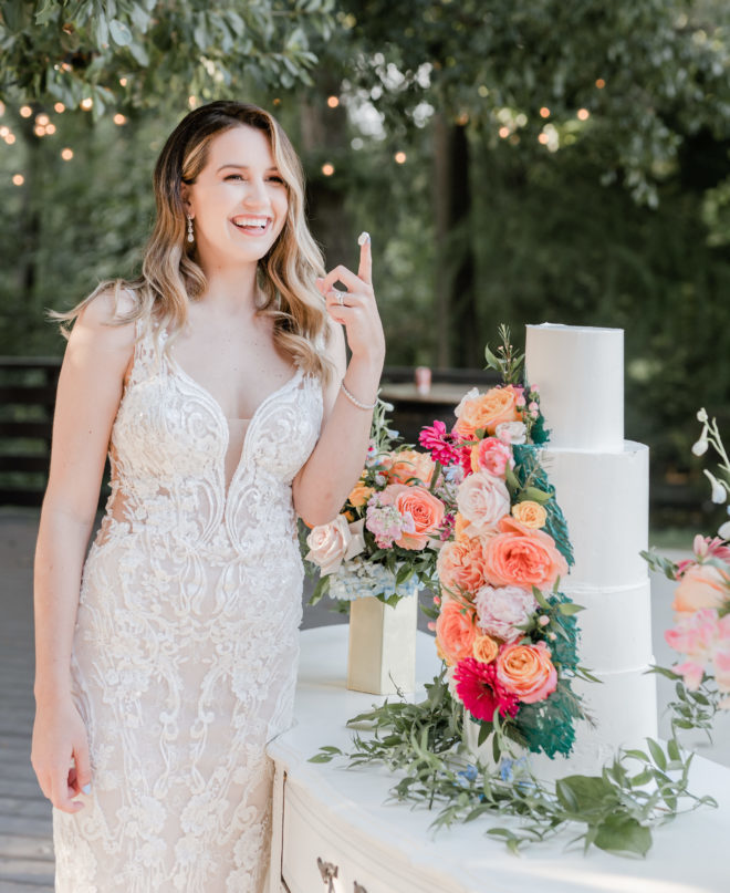 Woman in white fitted lace with plunging illusion neckline smiling in the distance while holding up a finger covered in icing next to a four tiered white wedding cake adorned with fresh florals atop a vintage dresser on the patio of the Carriage House wedding venue at a wedding styled shoot by Amy Maddox Photography.