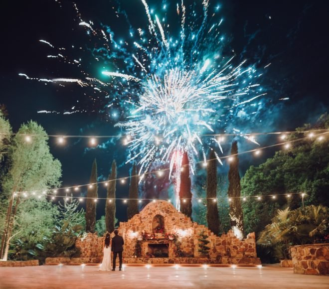 Bride and groom watching fireworks on outside patio of Madera Estates in Conroe, Texas