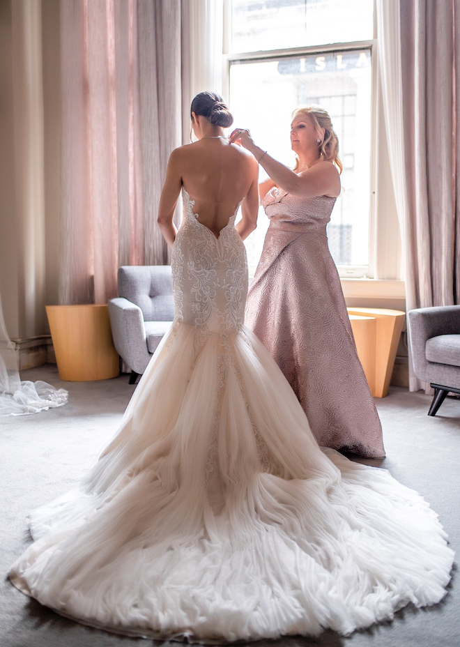 Mother of the bride is helping the bride get ready in an intimate bridal lounge at The Corinthian Houston.