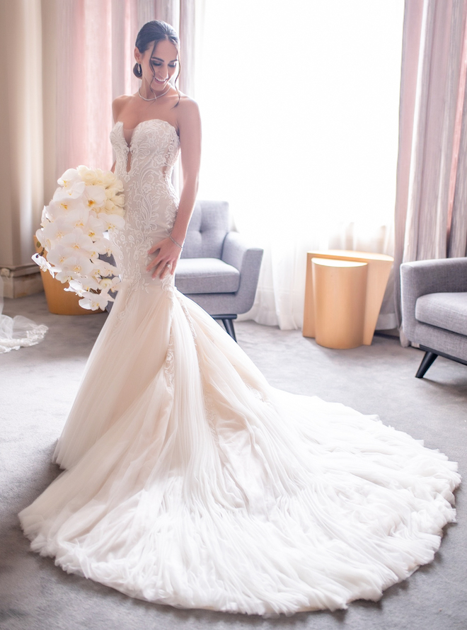 Bride in a fitted white mermaid wedding dress with an extended train.