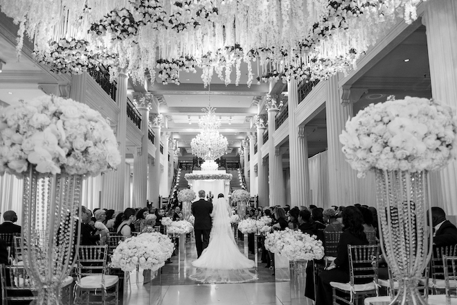 Father of the bride walking down the aisle with his daughter in a ballroom decorated in white florals.
