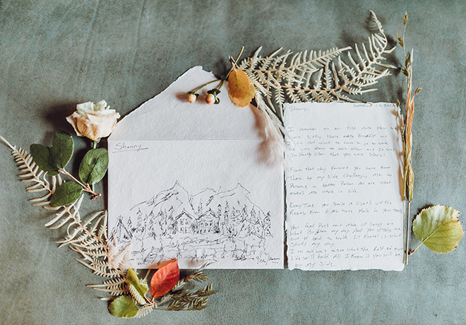 """Envelope with hand illustrated picture of woods and mountains with the name """"Shanny"""" on it next to a hand-written letter surrounded by dried florals and leaves."""