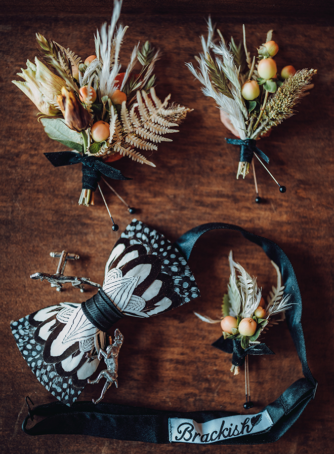 The groom's black and white feather bowtie rests next to dog-shaped cufflinks and wedding boutonnieres of autumn colored botanicals and small grass plumes.