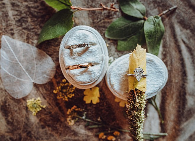 Yellow wildflowers, two green leaves and a white aspen leaf surround two velvet ring boxes holding a diamond wedding band, a solid gold wedding band, and a pear shaped diamond engagement ring.