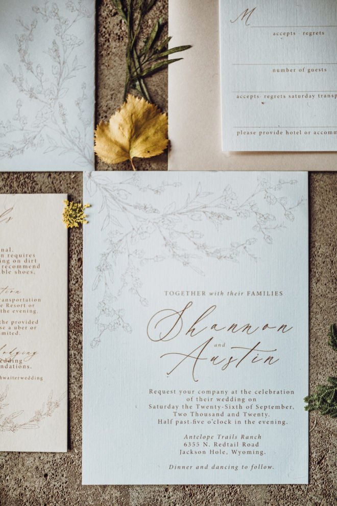 """Dried botanicals surround a white and cream colored invitation suite including a white invitation with a light gray floral motif that reads, """"Together with their Families Shannon and Austin request your company at the celebration of their wedding"""""""