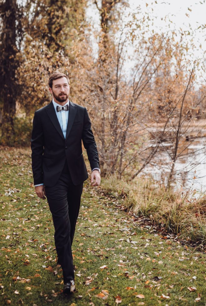 Groom wearing black suit with feather bowtie walks down a leaf strewn grass path aside Snake River at his wedding in Jackson Hole, Wyoming.
