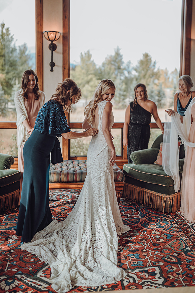 The mother of the bride finishes buttoning her daughter's wedding dress before her fall wedding.