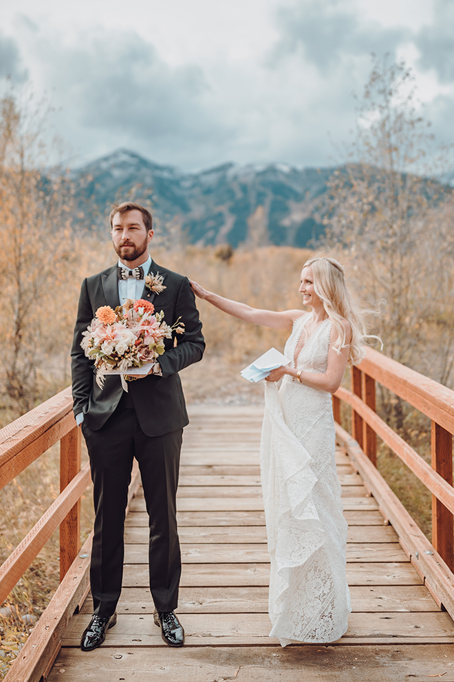 A bride taps her groom on the shoulder before their first look while standing on a bridged with the Teton mountians in the background.