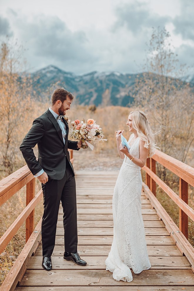 Groom in black suit with blue undershirt holding bouquet of florals smiles at a smiling bride in a long lace fitted gown while standing on an outdoor bridge with the Grand Teton mountains behind them in Jackson Hole, Wyoming.