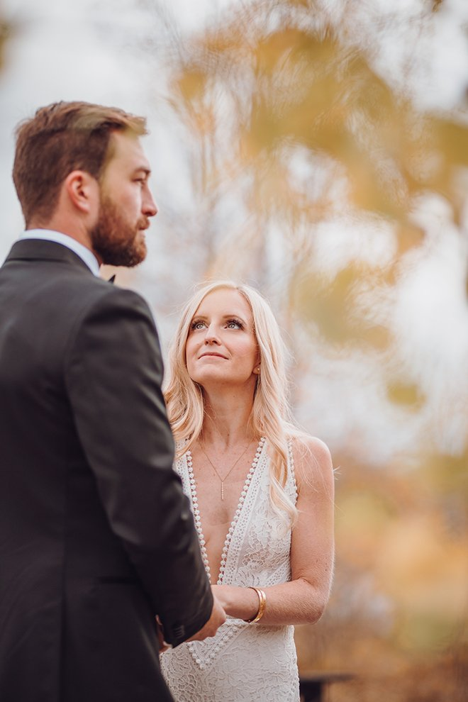A smiling blonde bride looks up at a groom during their alfresco wedding ceremony in Jackson Hole, Wyoming.