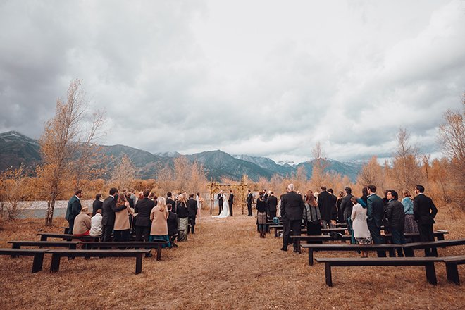 Jackson Hole, Wyoming Outdoor wedding with bride and groom under an altar of aspens aside Snake River with the Grand Tetons in the background.