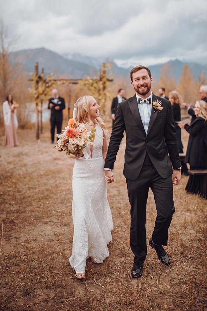 A bride and groom walk hand in hand after their wedding ceremony with an aspen-adorned altar and the Teton mountains in the background as their guests clap.