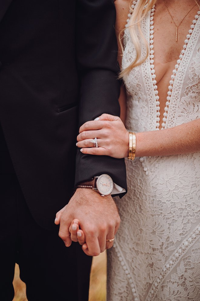 """A bride in a plunging neckline wedding dress holds hands with her groom, showing their wedding bands after saying """"I do."""""""