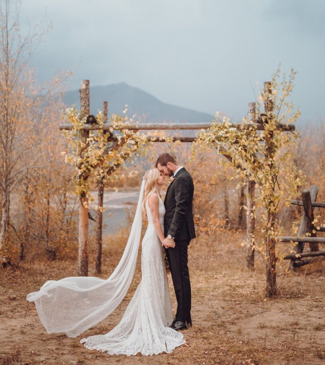 Bride, in long fitted lace white wedding gown and long veil, stands forehead to forehead with a groom, wearing a black suit, in front of an altar created from golden-leafed aspens beside the Snake River in a Jackson Hole wedding ceremony.