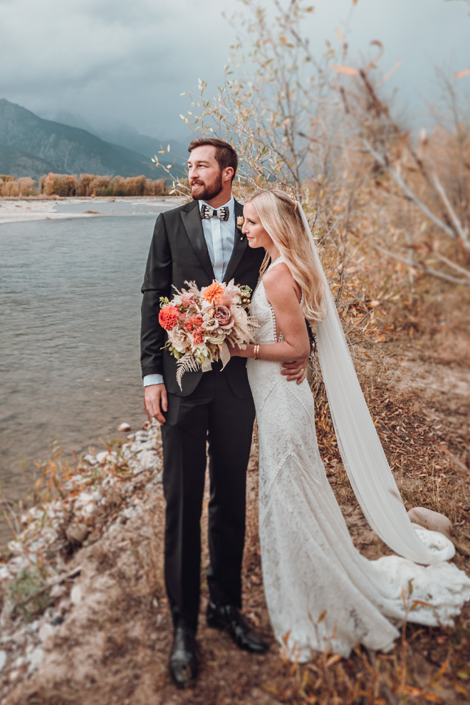 The bride and groom embrace overlooking the Snake River in Jackson, Wyoming while the bride holds her fall wedding bouquet.