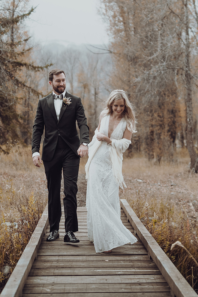 Groom holds hands with a smiling bride while walking across a wooden bridge at their autumn wedding in Jackson Hole, Wyoming.