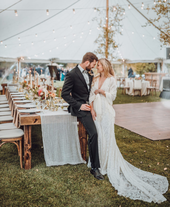 Groom scrunches his face and smiles at a smiling bride in long white gown and white shaw inside of a tent decorated with string lights, aspen trees and wooden guest tables set with lit candles and florals in a Jackson Hole, Wyoming.