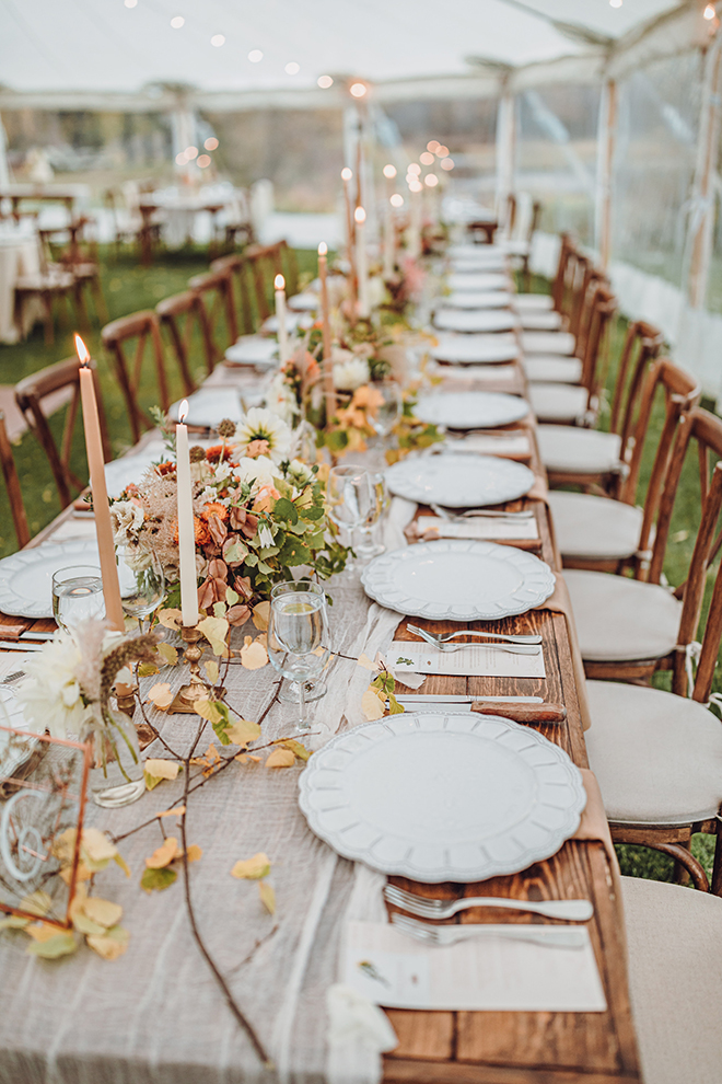 A long table is decorated with bud vases, aspen sprigs, and tall candlesticks during a tented reception.