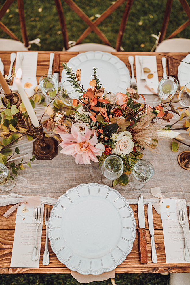 The wedding photographer captures the beautiful fall wedding reception table from above.