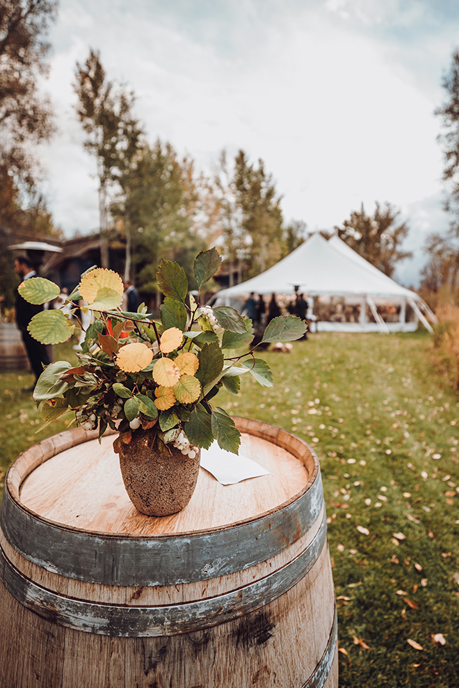 A wine barrel adorned with sprigs of aspen leaves and berries rests atop a wine barrel with a tented reception in the background.