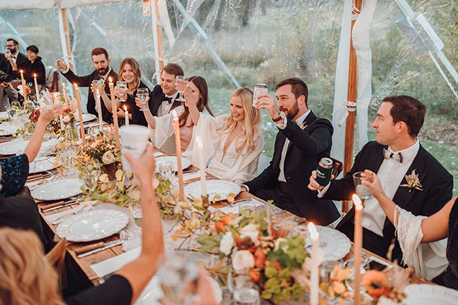 The bride and groom join their friends and family for a toast while seated in the center of a long reception table adorned with fall blooms and aspen sprigs.