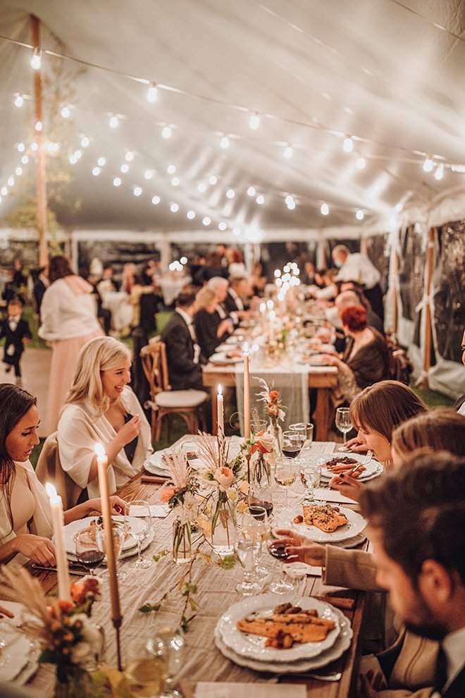 Seated guests at a long reception table adorned with lit tapered candles and florals underneath string lights inside a tent at a Jackson Wyoming wedding.
