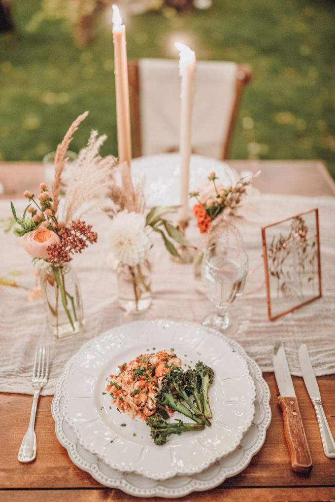 Place setting with white scalloped plate and charger topped with a green vegetable and a serving of meat on a wooden table set with small bud vases filled with pink, mauve and cream colored botanicals, two lit tapered candles and a frame showcasing pressed florals at a Jackson Hole, Wyoming wedding.