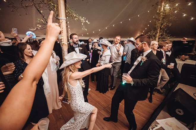 A bride wearing a sequin cowboy hat and dress dances and points at a groom wearing glasses made of glow sticks inside a reception tent during an intimate Jackson Hole Wyoming wedding.