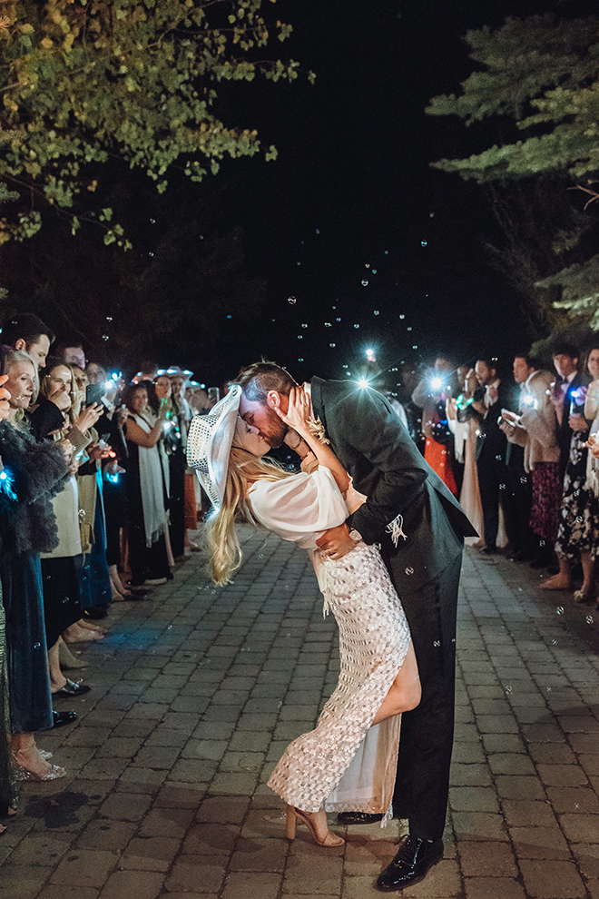 Bride in white fitted gown with deep slit and white glittered cowboy hat kisses groom during a their wedding send-off at their Jackson Wyoming wedding.