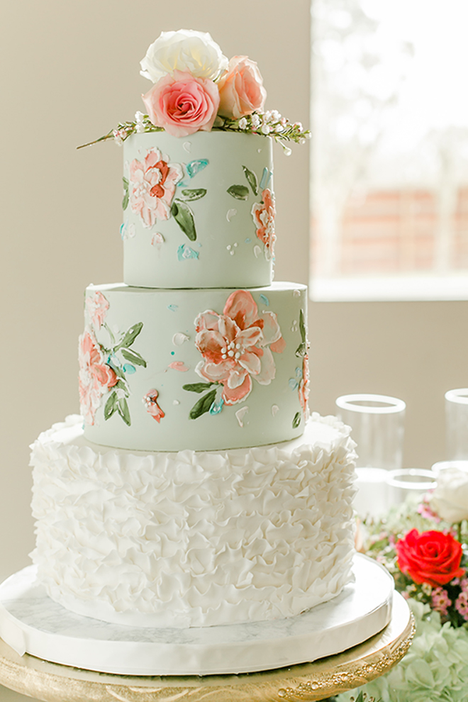 A beautiful three-tier wedding cake begins with a sculpted, ruffled white layer and is stacked with two more aqua-frosted layers with peach and blush floral details, by Common Bond.