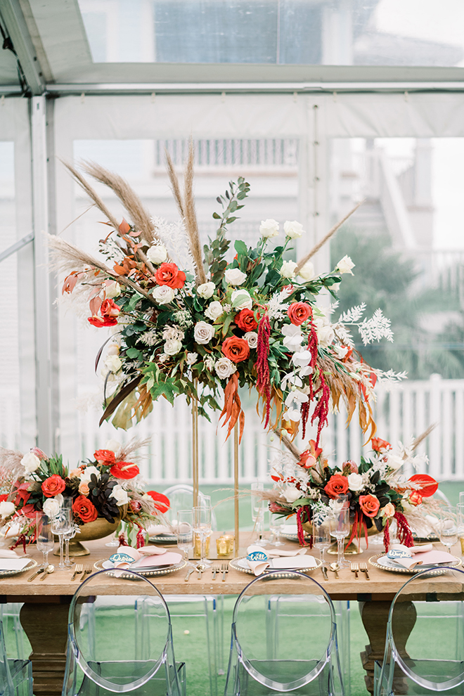 The sunset colored wedding palette pops with cascading floral arrangements of orange, red, and blush flowers with long sprigs of tan pampas grass.
