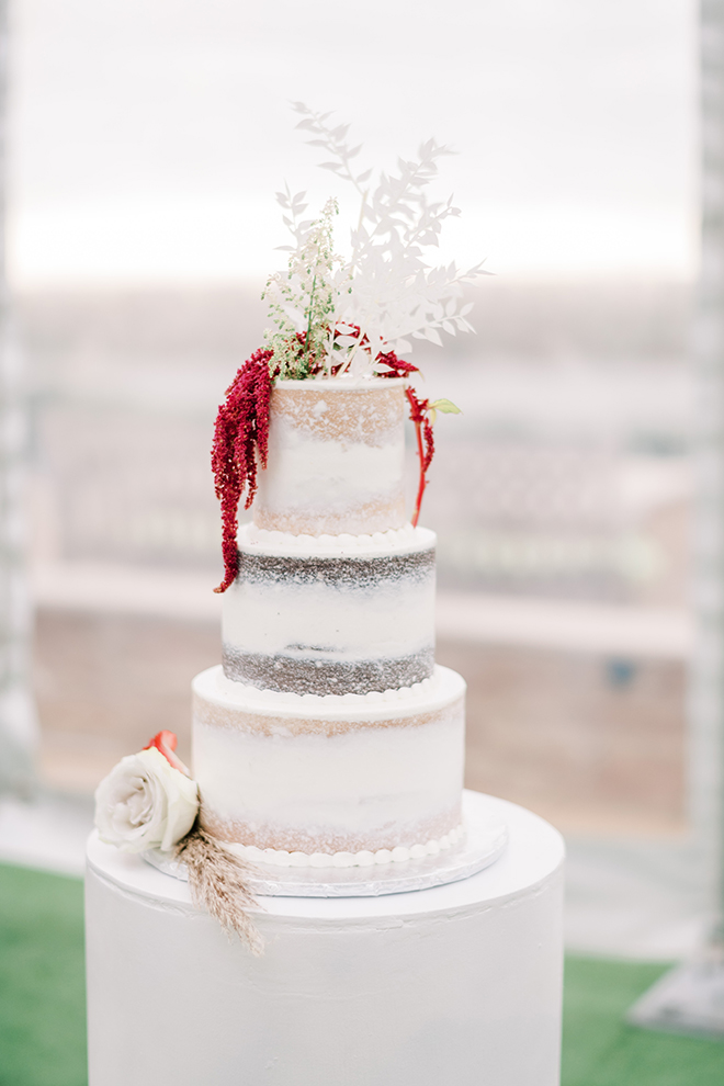 A three-tiered naked wedding cake by Susies Cakes is adorned with a white rose bloom and a blade of pampas grass, including red Amaranthus and white botanicals on the top tier.