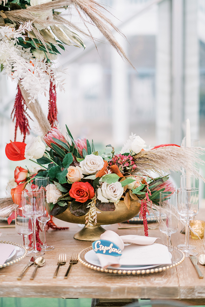Small organic floral centerpiece in footed gold bowl aside a large pampass grass adorned with red,white and green botanicals atop a washed wood reception table set with gold adorned place settings and tall tapered candles.