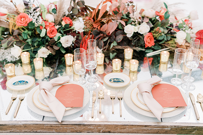 A closeup of the brides and grooms reception table with vibrant florals, coral-colored menus, and teal agate slices that say bride and groom.