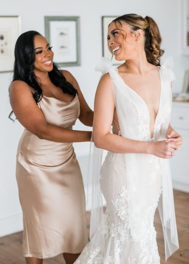 Bridesmaid with long curled hair and short silk blush dress buttoning the brides white Galia Lahav gown with a deep plunging neckline and tied straps, while the bride smiles back.