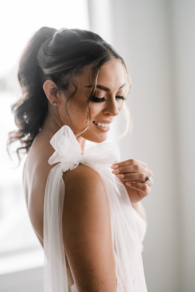 The brides dress has a sweet tulle bow on the right shoulder as natural light casts an ethereal glow over her.